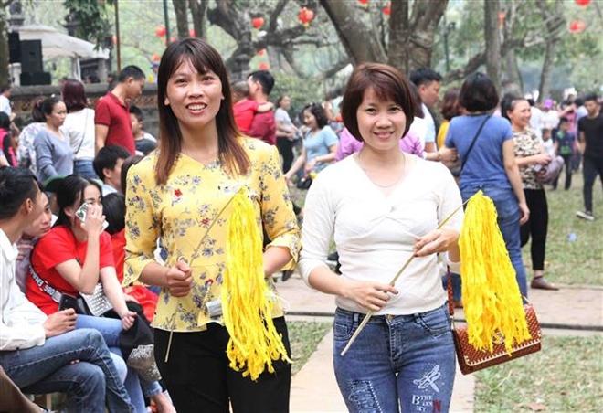 Trong ảnh: Người dân xin lộc hoa tre trong ngày hội cầu mong một năm sức khỏe, may mắn…Ảnh: Quang Quyết-TTXVN