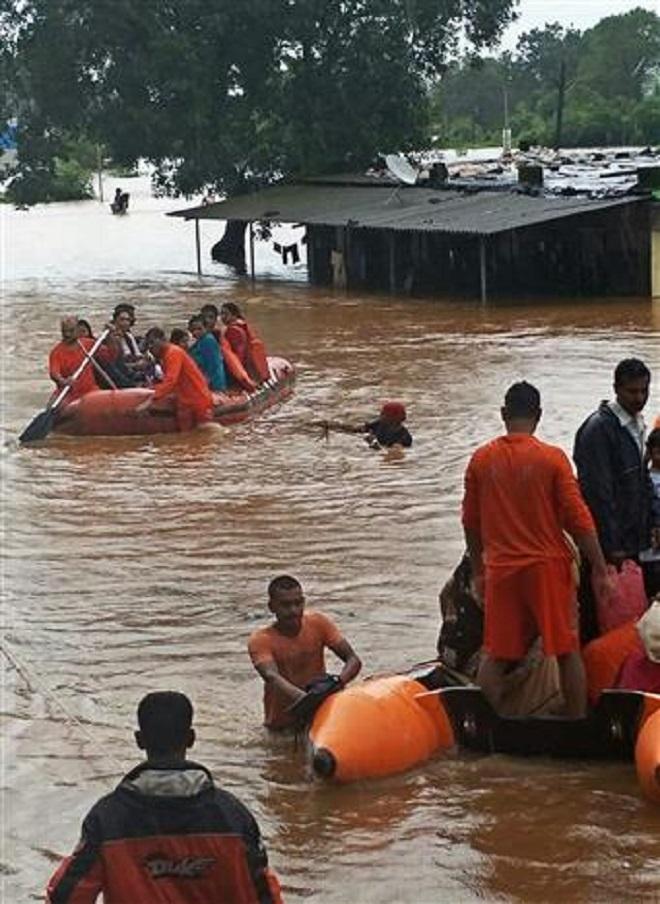 Trong ảnh: Lực lượng cứu hộ giải cứu hành khách trên chuyến tàu mắc kẹt trong lũ gần thành phố Mumbai, Ấn Độ ngày 27/7/2019. Ảnh: AFP/TTXVN
