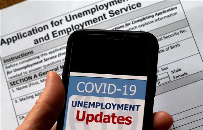 Trong ảnh: Cập nhật tình hình mất việc làm do dịch COVID-19 trên điện thoại tại Arlington, bang Virginia, Mỹ, ngày 8/5/2020. Ảnh: AFP/TTXVN