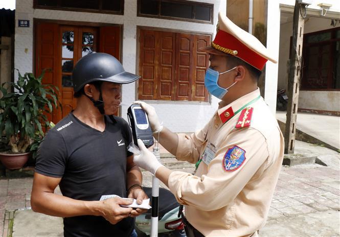 Trong ảnh: Lực lượng Cảnh sát giao thông huyện Văn Bàn (Lào Cai) thực hiện khiểm tra nồng độ cồn với người tham gia giao thông trên địa bàn Thị trấn Khánh Yên. Ảnh: Quốc Khánh - TTXVN
