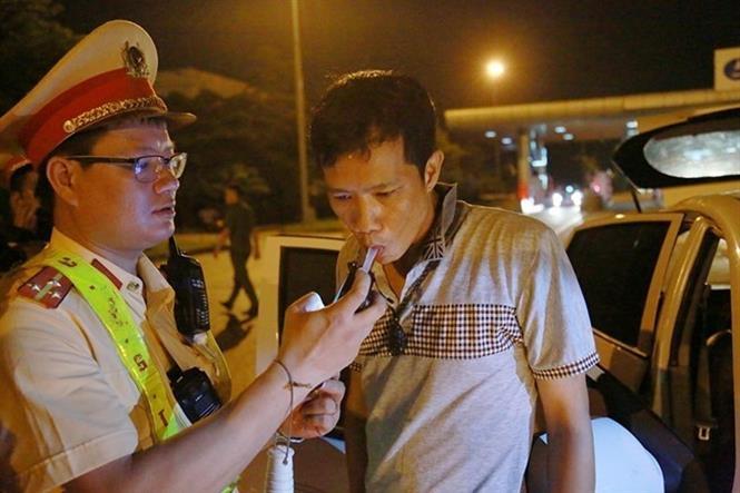 Trong ảnh: Cảnh sát giao thông kiểm tra nồng độ cồn của tài xế Lưu Hồng Quân. Ảnh: TTXVN phát