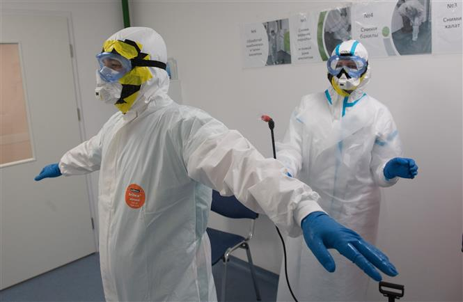 Trong ảnh: Nhân viên y tế khử trùng quần áo bảo hộ tại khu vực điều trị bệnh nhân COVID-19 ở Moskva, Nga, ngày 14/5/2020. Ảnh: THX/TTXVN