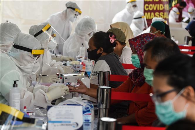 Trong ảnh: Nhân viên y tế lấy mẫu xét nghiệm COVID-19 cho người dân tại Nam Tangerang, Indonesia ngày 14/5/2020. Ảnh: THX/TTXVN