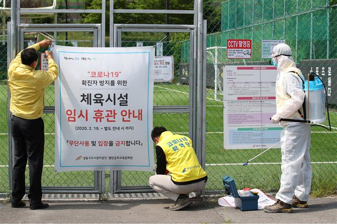 Trong ảnh: Nhân viên dỡ tấm biển đóng cửa tạm thời do dịch COVID-19 tại một sân bóng đá ở Seoul, Hàn Quốc, ngày 4/5/2020. Ảnh: YONHAP/TTXVN