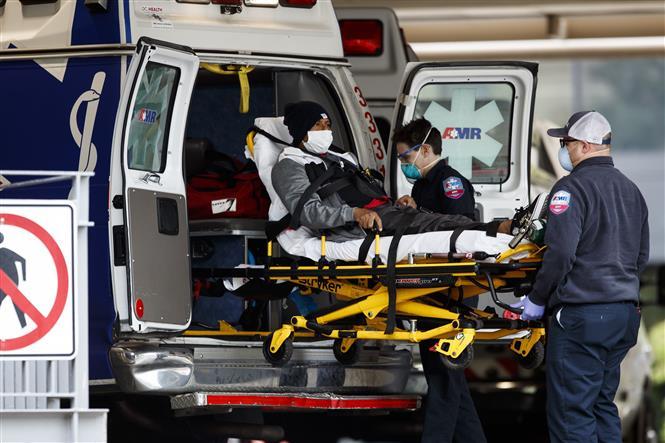 Trong ảnh: Nhân viên y tế chuyển bệnh nhân COVID-19 tới bệnh viện Đại học George Washington ở Washington D.C., Mỹ, ngày 27/4/2020. Ảnh: THX/ TTXVN