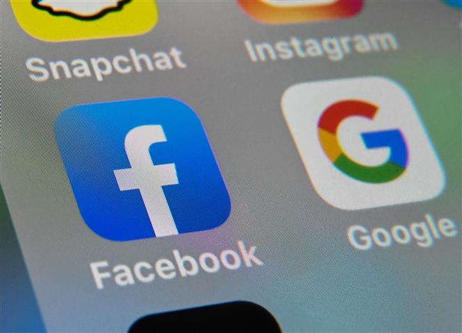 Trong ảnh: Biểu tượng của Facebook và Google trên một màn hình máy tính bảng. Ảnh: AFP/TTXVN