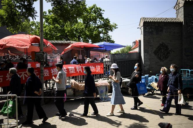 Trong ảnh: Người dân xếp hàng thực hiện biện pháp giãn cách xã hội khi vào chợ tại Bắc Kinh, Trung Quốc, ngày 10/5/2020. Ảnh: AFP/TTXVN