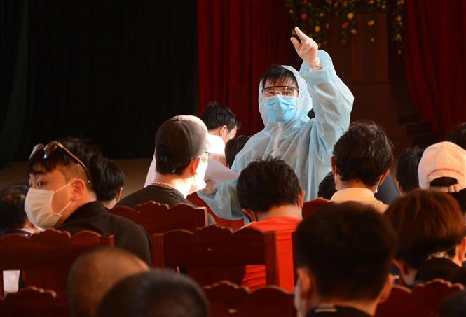Trong ảnh: Nhân viên y tế hướng dẫn các công dân trở về từ Hàn Quốc về nội quy cách ly. Ảnh: Văn Dũng - TTXVN