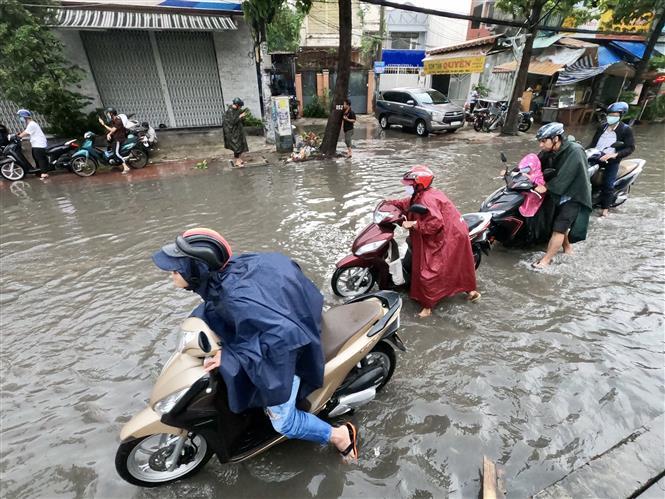 Trong ảnh: Nước ngập cao khiến hàng loạt phương tiện bị chết máy phải dẫn bộ. Ảnh: TTXVN phát.
