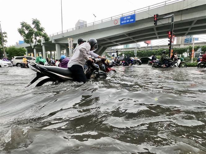 Trong ảnh: Nước ngập nhiều nơi đến hơn nửa mét khiến người dân di chuyển hết sức khó khăn. Ảnh: Hồng Giang - TTXVN