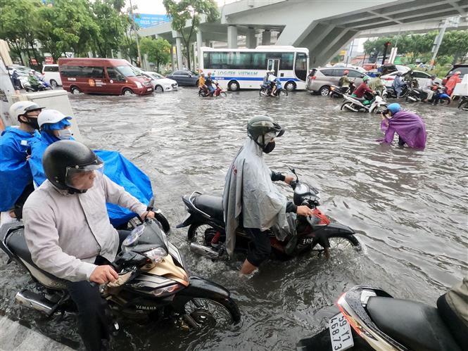 Trong ảnh: Người dân vất vả lưu thông trên tuyến đường bị ngập. Ảnh: Hồng Giang - TTXVN.