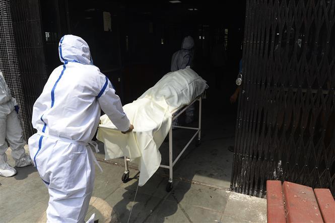 Trong ảnh: Nhân viên y tế chuyển thi thể bệnh nhân mắc COVID-19 tới khu vực hỏa táng tại New Delhi, Ấn Độ ngày 3/6/2020. Ảnh: AFP/TTXVN