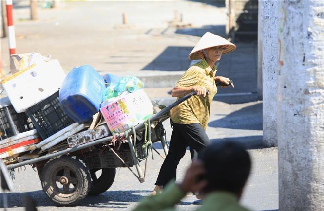 Trong ảnh: Người lao động Thủ đô vất vả với nắng nóng gay gắt (ảnh chụp sáng 22/6/2020). Ảnh: Thành Đạt - TTXVN