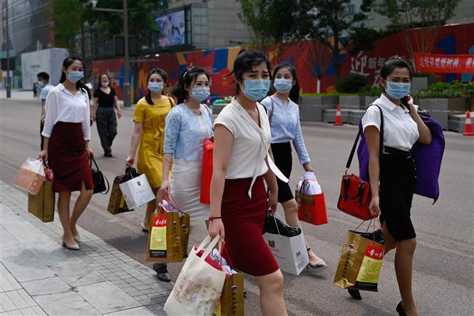 Trong ảnh: Người dân đeo khẩu trang phòng dịch COVID-19 tại Bắc Kinh, Trung Quốc ngày 23/6/2020. Ảnh: AFP/TTXVN