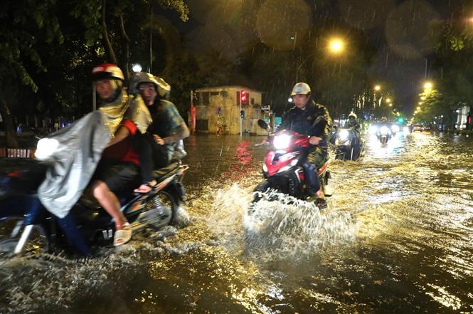 Trong ảnh: Mưa lớn khiến một số tuyến đường ngập úng, gây khó khăn cho người tham gia giao thông. Ảnh: Thành Đạt - TTXVN