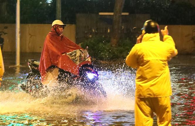 Trong ảnh: Nhân viên thoát nước nhắc nhở người tham gia giao thông không đi vào chỗ ngập sâu. Ảnh: Thành Đạt - TTXVN
