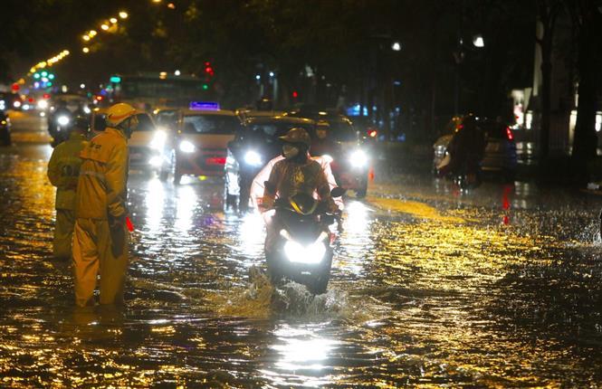 Trong ảnh: Nhân viên thoát nước phân luồng nhắc nhở người tham gia giao thông không đi vào chỗ ngập sâu trên đường Lý Thường Kiệt - Phan Bội Châu. Ảnh: Thành Đạt - TTXVN