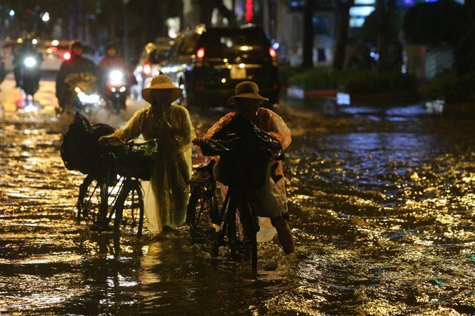 Trong ảnh: Mưa lớn trên đường Lý Thường Kiệt - Phan Bội Châu gây khó khăn cho người tham gia giao thông. Ảnh: Thành Đạt - TTXVN