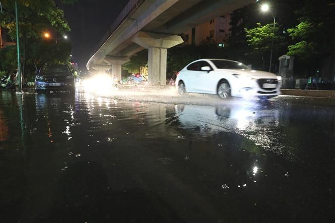 Trong ảnh: Cơn mưa giảm nhiệt chiều tối 10/6 (đường Hào Nam). Ảnh: Thành Đạt - TTXVN