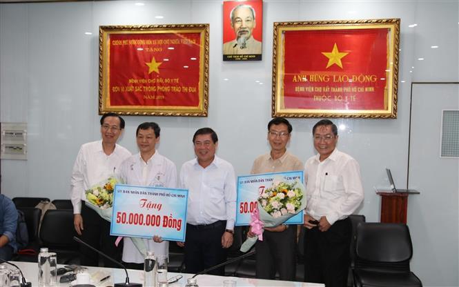 Trong ảnh: Chủ tịch UBND Thành phố Hồ Chí Minh Nguyễn Thành Phong tặng quà động viên cho đại diện Bệnh viện Chợ Rẫy và Bệnh viện Bệnh Nhiệt đới. Ảnh: Đinh Hằng - TTXVN