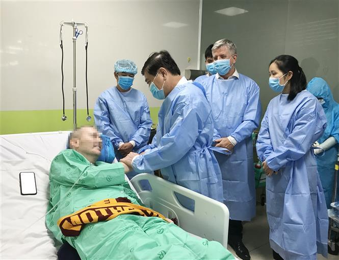 Trong ảnh: Chủ tịch UBND Thành phố Hồ Chí Minh Nguyễn Thành Phong nói chuyện, bắt tay với bệnh nhân 91. Ảnh: TTXVN phát