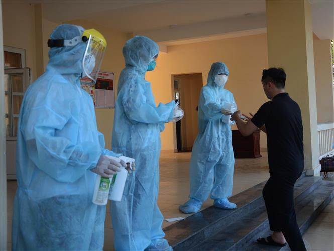 Trong ảnh: Nhân viên y tế khử trùng tay, phát khẩu trang y tế cho công dân trở về từ Hàn Quốc. Ảnh: Văn Dũng - TTXVN