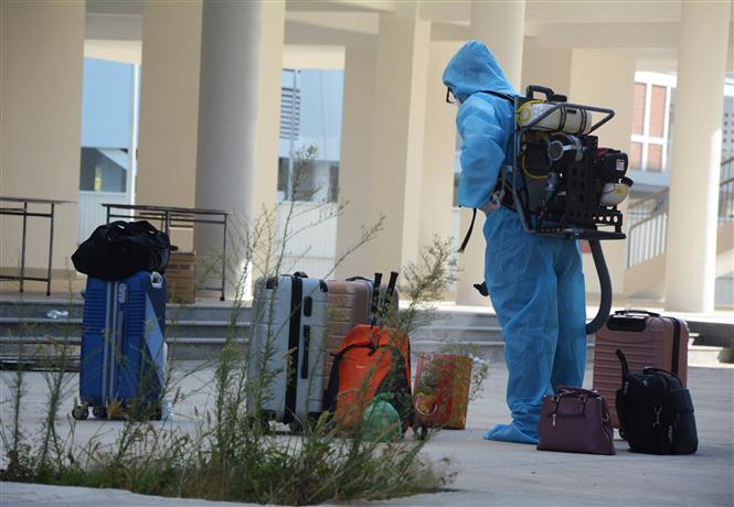Trong ảnh: Nhân viên y tế phun khử trùng đồ dùng của các trường hợp F1 được cách ly tại khu ký túc xá phía Tây thành phố Đà Nẵng. Ảnh: Văn Dũng - TTXVN