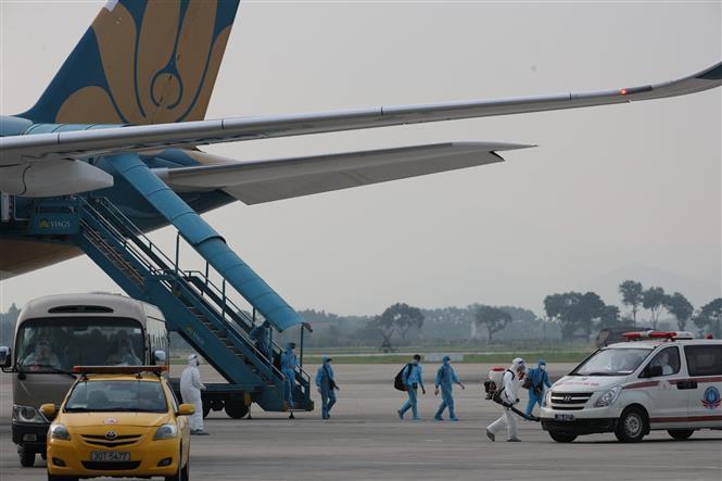 Trong ảnh: Các công dân xuống máy bay vào xe để về khu cách ly y tế. Ảnh: Thành Đạt - TTXVN