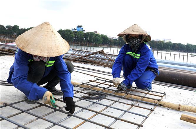 Trong ảnh: Công nhân đang làm việc tại Dự án Đầu tư xây dựng tuyến đường vành đai 3 đi thấp qua hồ Linh Đàm và nhánh kết nối với đường vành đai 3. Ảnh: Văn Điệp - TTXVN