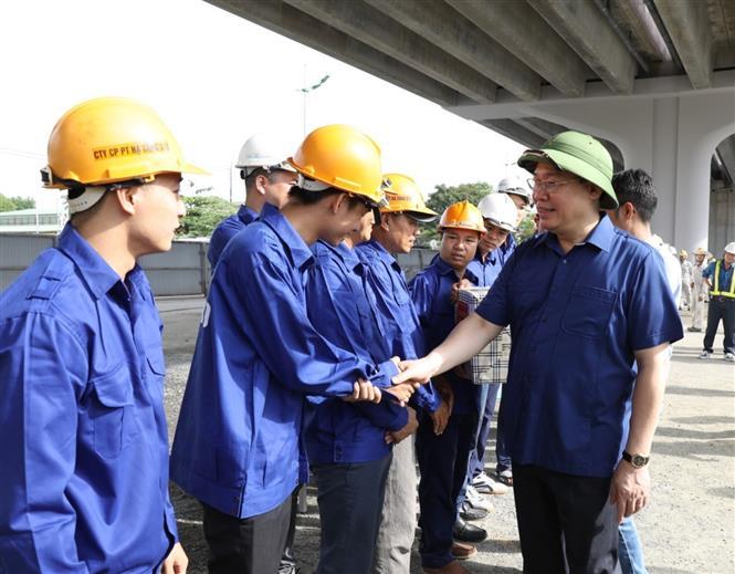 Trong ảnh: Bí thư Thành ủy Hà Nội Vương Đình Huệ thăm hỏi cán bộ, công nhân đang làm việc tại Dự án Vành đai 3 đoạn Mai Dịch - cầu Thăng Long. Ảnh: Văn Điệp - TTXVN