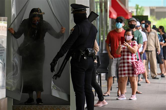 Trong ảnh: Cảnh sát gác bên ngoài một trung tâm mua sắm để nhắc nhở người dân thực hiện tốt các biện pháp phòng dịch COVID-19 tại Manila, Philippines. Ảnh: AFP/TTXVN