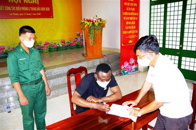 Đối tượng Ekwegbalu James Nzube (áo đen) bị tạm giữ tại Đồn Biên phòng Cửa khẩu quốc tế Mộc Bài. Ảnh: Thanh Tân - TTXVN