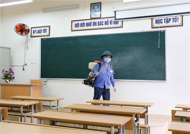 Trong ảnh: Phun thuốc khử khuẩn địa điểm tổ chức thi tốt nghiệp. Ảnh: Thanh Tùng - TTXVN