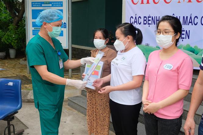 Trong ảnh: Đại diện Bệnh viện dã chiến Hòa Vang trao giấy xuất viện cho bệnh nhân. Ảnh: Văn Dũng - TTXVN