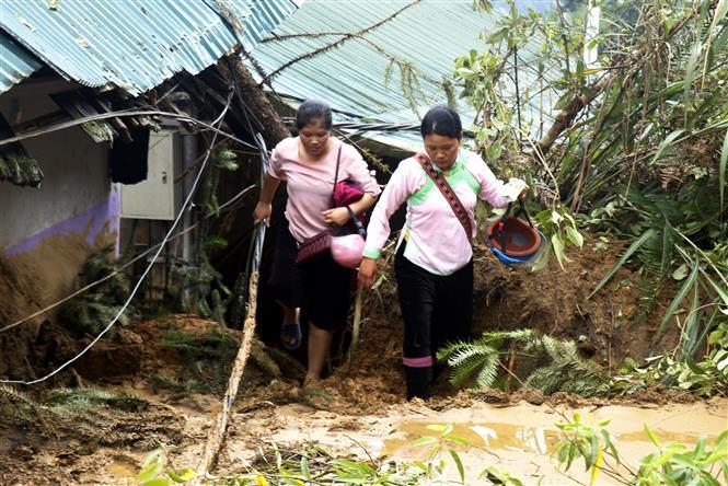 Trong ảnh: Người dân đi lại rất khó khăn do sạt lở đất tại thị xã Sa Pa. Ảnh: Quốc Khánh - TTXVN