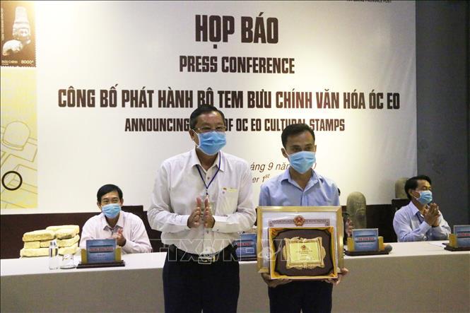 Phó Chủ tịch UBND tỉnh An Giang Lê Văn Nưng (bìa trái) trao Bằng khen của UBND tỉnh kèm Logo cho đại diện của họa sĩ Nguyễn Du tác giả của bộ tem Văn hóa Óc Eo. Ảnh: Công Mao -TTXVN