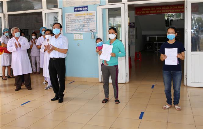 Lãnh đạo Sở Y tế Quảng Trị trao giấy xác nhận hoàn thành thời gian cách ly y tế phòng, chống dịch COVID-19 cho 2 bệnh nhân. Ảnh: Hồ Cầu-TTXVN