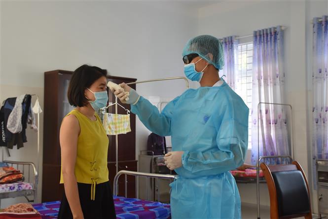 Điều dưỡng tại Khu cách ly tập trung của tỉnh Bà Rịa-Vũng Tàu kiểm tra thân nhiệt của người cách ly tập trung. Ảnh: Hoàng Nhị - TTXVN