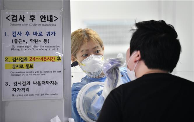 Nhân viên y tế lấy mẫu xét nghiệm COVID-19 cho người dân tại Seoul, Hàn Quốc ngày 18/8/2020. Ảnh: AFP/TTXVN