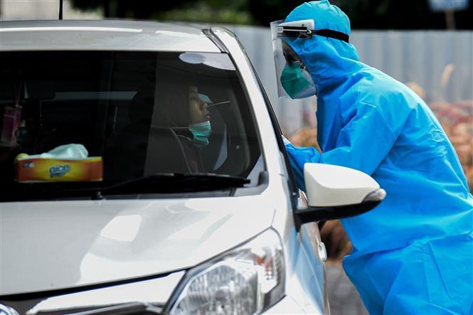 Nhân viên y tế lấy mẫu xét nghiệm COVID-19 cho người dân tại Jakarta, Indonesia ngày 9/10/2020. Ảnh: THX/TTXVN