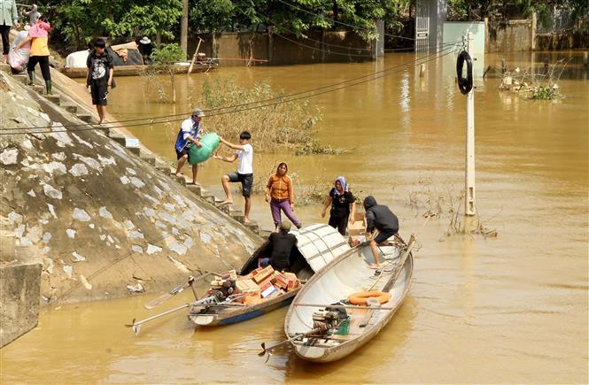 Các đoàn cứu trợ tập trung đưa những mặt hàng thiết yếu đến vùng bị nước lũ cô lập ở các xã của huyện Quảng Ninh, tỉnh Quảng Bình. Ảnh: Văn Tý-TTXVN
