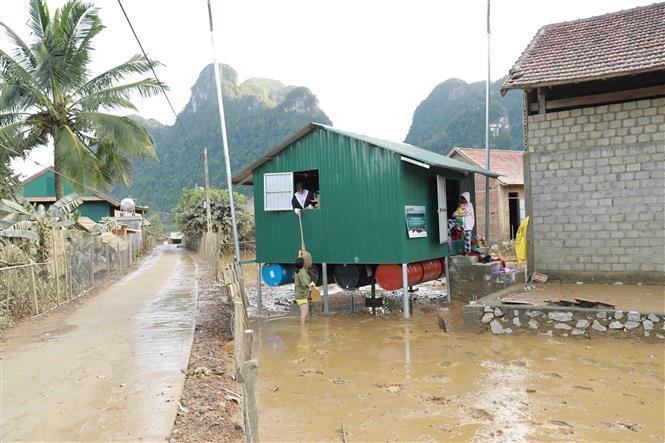 Người dân dọn dẹp vệ sinh môi trường quanh khu vực nhà chống lũ của gia đình. Ảnh: Vũ Sinh - TTXVN