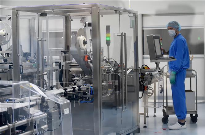 Nhân viên làm việc trên dây chuyền sản xuất vaccine ngừa COVID-19 tại một công ty công nghệ sinh học ở Strelna, Nga ngày 20/5/2020. Ảnh: AFP/TTXVN