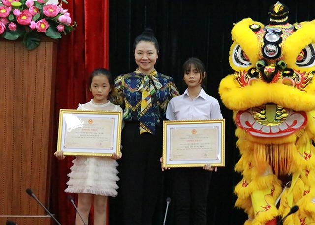 NSND Vũ Thuý Ngần – nguyên GĐ Trung tâm thể nghiệm ĐH Sân khấu Điện ảnh trao giải Tài năng trẻ cho em Nguyễn Thị Quyên (huyện Quốc Oai – bên phải) và em Lê Thị Mai Anh (quận Cầu Giấy – bên trái).