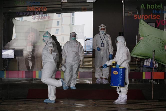 Nhân viên phun thuốc khử trùng nhằm ngăn chặn sự lây lan của dịch COVID-19 tại Jakarta, Indonesia. Ảnh: THX/TTXVN