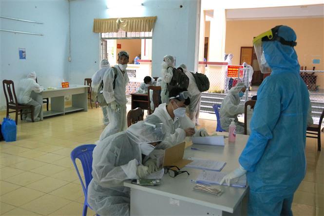 Các công dân kiểm tra y tế và làm thủ tục khai báo y tế tại buổi tiếp nhận. Ảnh: Chanh Đa-TTXVN