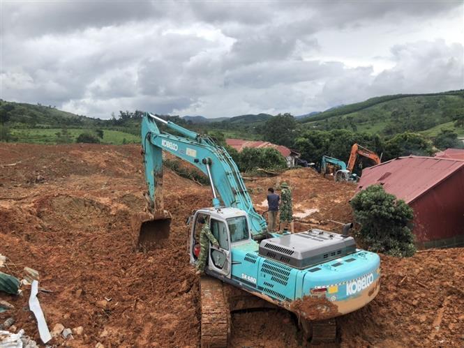 Phương tiện cơ giới khẩn trương đào bới tìm kiếm người bị vùi lấp. Ảnh: TTXVN phát