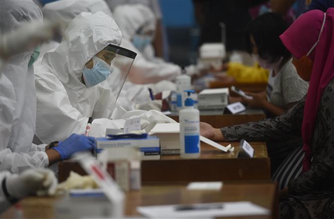 Trong ảnh: Nhân viên y tế lấy mẫu xét nghiệm COVID-19 cho người dân tại Jakarta, Indonesia ngày 23/11/2020. Ảnh: THX/TTXVN