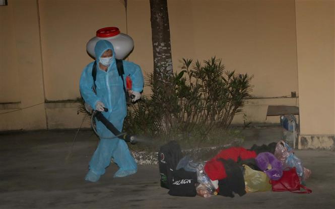 Phun khử khuẩn đồ dùng cá nhân của sinh viên Lào. Ảnh: Thanh Hải - TTXVN