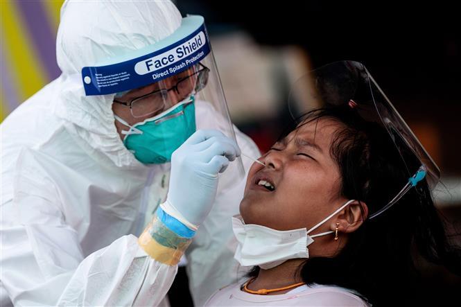Trong ảnh: Nhân viên y tế lấy mẫu xét nghiệm COVID-19 cho người dân tại Samut Sakhon, Thái Lan, ngày 19/12/2020. Ảnh: AFP/TTXVN